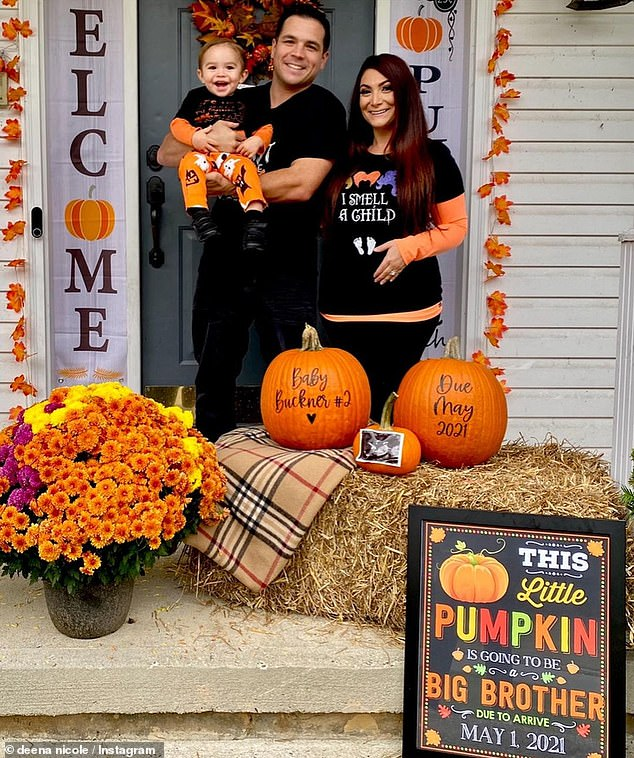 Halloween vibes:With shades of orange, black, and purple dominating the setting, the family surrounded themselves with pumpkins, haystacks, and wreaths made of fall toned leave