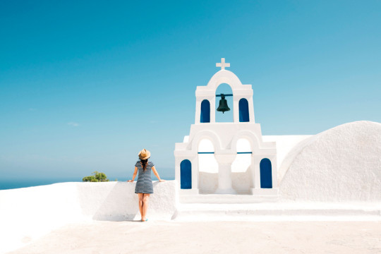 Greece, Santorini, Oia, back view of woman standing next to bell tower looking to the sea