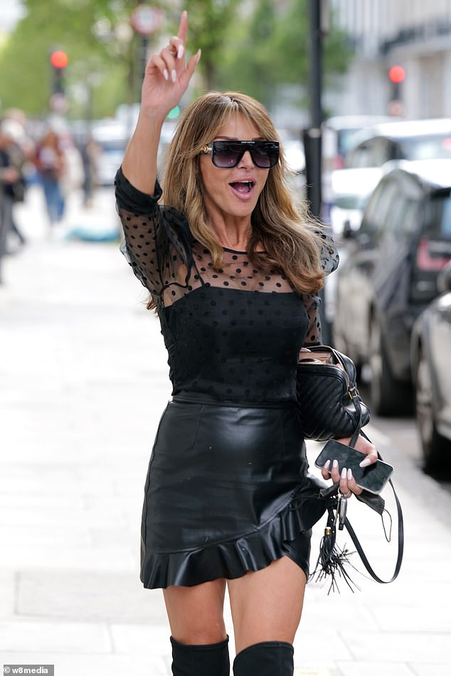 Lizzie showcased her sense of style on the outing, donning a black top with a sheer detail and polka dot print
