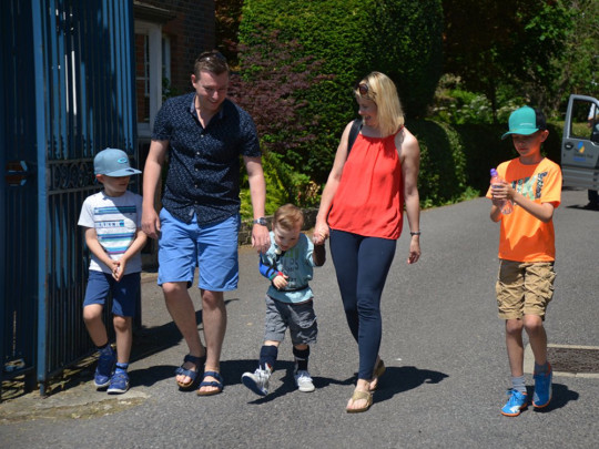 Josh with his family walking out of The Children's Trust. PA Real Life Collect
