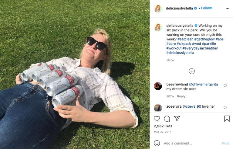 Bella Younger lies with six cans of lager on her stomach with a caption 'working on my six pack in the park'