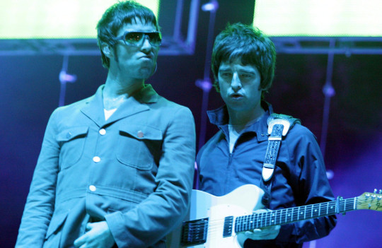 Liam Gallagher and Noel Gallagher performing as Oasis