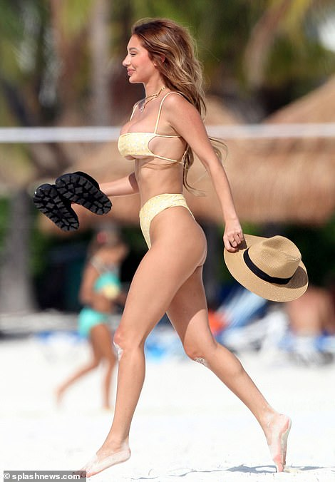 Frolicking: The Instagram model was seen making her way to a tanning spot with a hat and sandals
