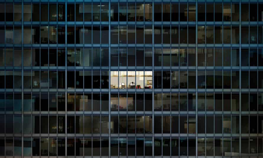 Up all hours: a worker burns the night oil in an empty office block.