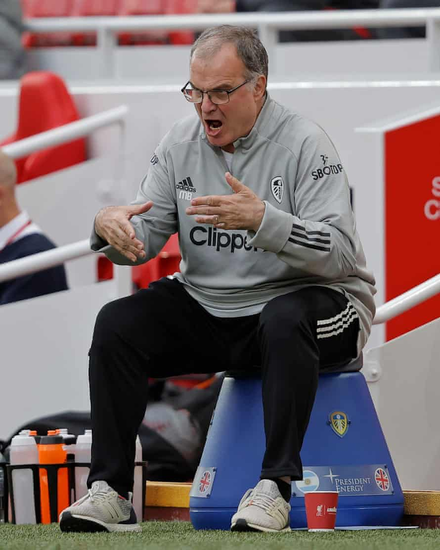 Marcelo Bielsa, head coach of Leeds United, gives orders while sitting on his bucket at Anfield.