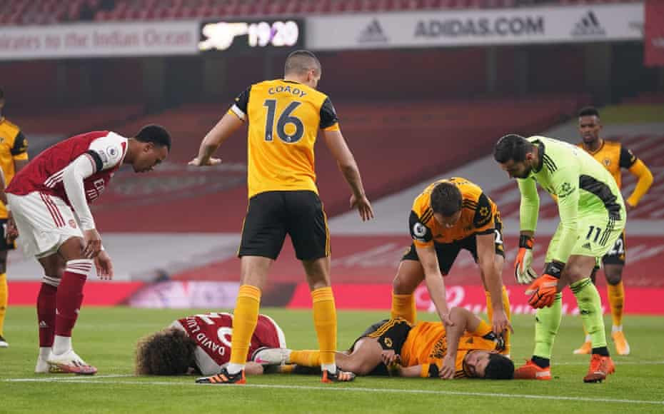 Raul Jimenez of Wolverhampton Wanderers and David Luiz of Arsenal receive help after a head collision.