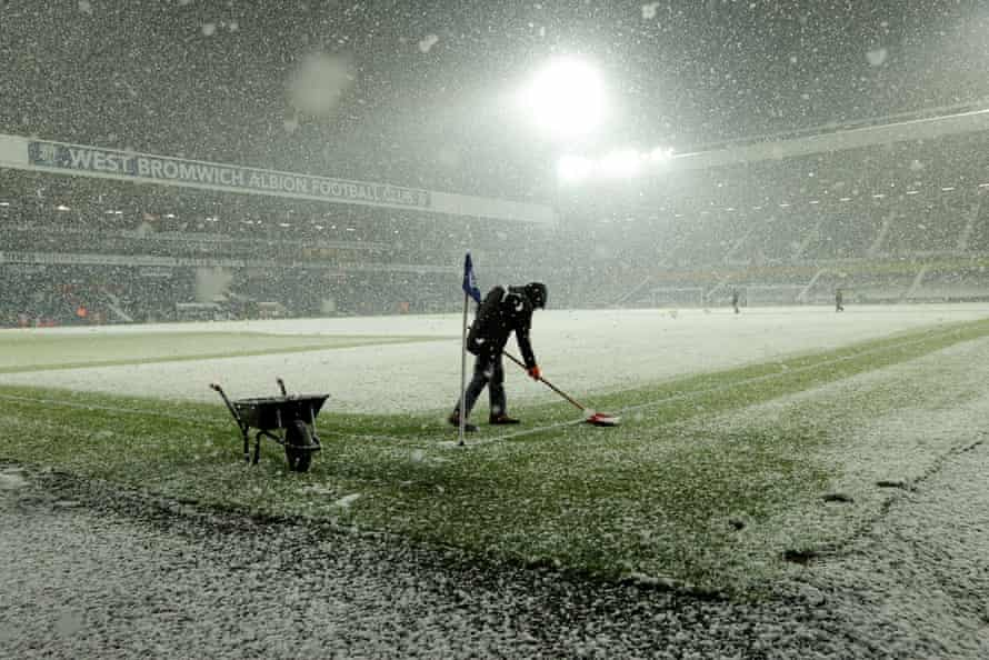 Heavy snow falls before the game between West Bromwich Albion and Arsenal at the Hawthorns as a groundsman try to clear the lines.