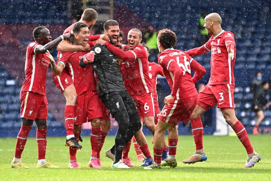 Alisson Becker of Liverpool is congratulated by his team-mates after scoring the winning goal against West Bromwich Albion.
