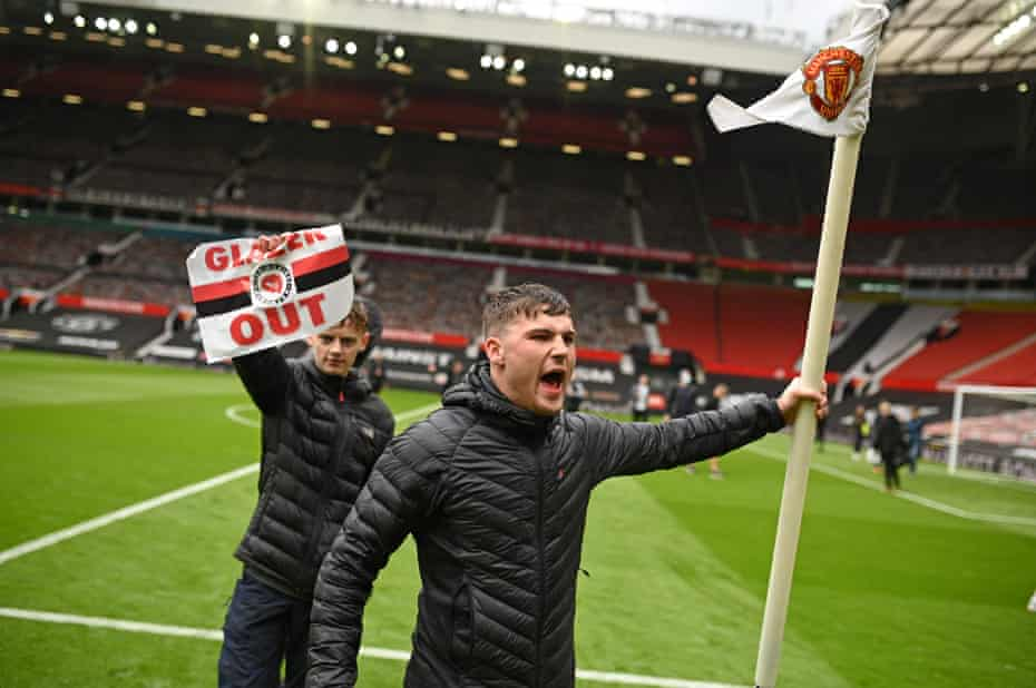 Football supporters protest against Manchester United's owners after breaking into Old Trafford. Their action caused the match with Liverpool to be cancelled.