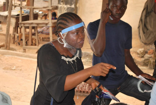 Damilola is wearing a protective visor as she calls from door to door handling out information on FGM