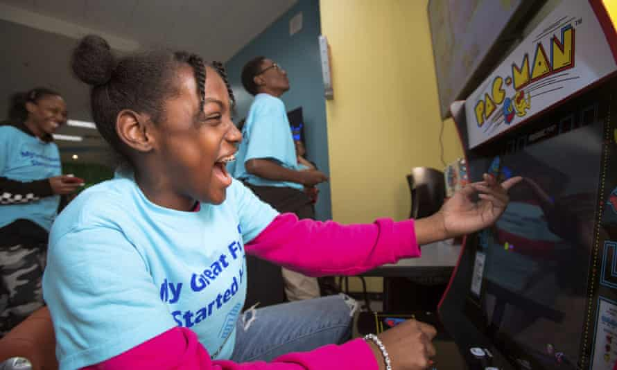 ayla plays Pac-Man during the unveiling of Aaron's $20,000 makeover of the teen center at Berkshire Partners Blue Hill Boys and Girls Club of Boston