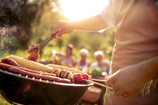 A man wearing an apron barbecuing some sausages, kebabs and corn, with people out of focus in the background sat at a picnic table.