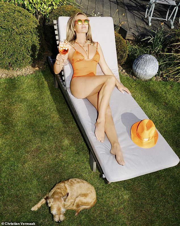 Garden party: Amanda Holden displayed her endless pins in a sexy orange bikini as she reclined with a cocktail in hand after confirming she's signed up for a new Channel 4 series
