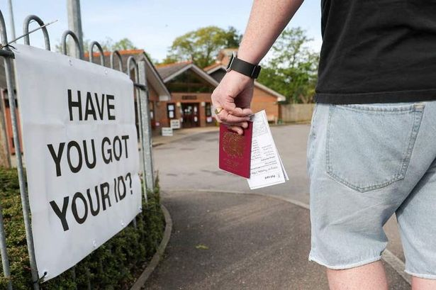 A voter carries his passport as photo ID outside a polling station