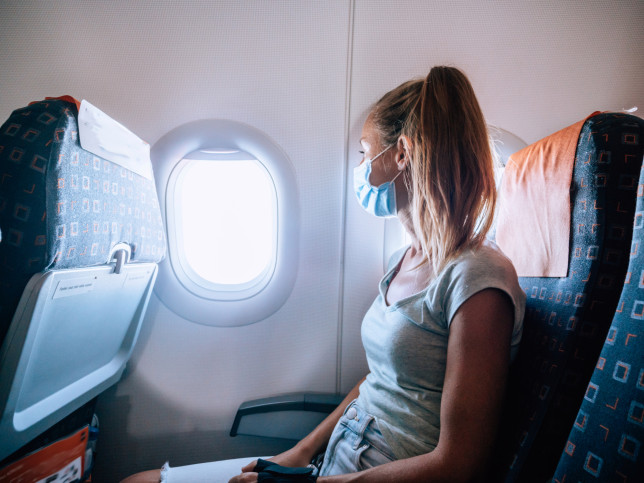 Woman traveling by plane  wearing face mask