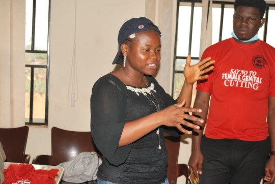 Damilola is giving an educational talk on FGM while her colleague is wearing a t-shirt that reads 'say no to female genital cutting'