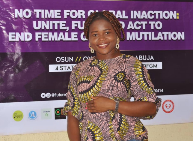 Damilola Okunola standing in front of an anti-FGM campaign sign