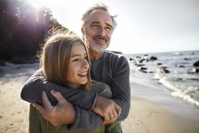 dad hugs his daughter on the beach