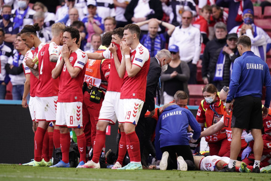 Denmark's players react as paramedics attend to Denmark's midfielder Christian Eriksen after he collapsed on the pitch during the UEFA EURO 2020 Group B football match between Denmark and Finland at the Parken Stadium