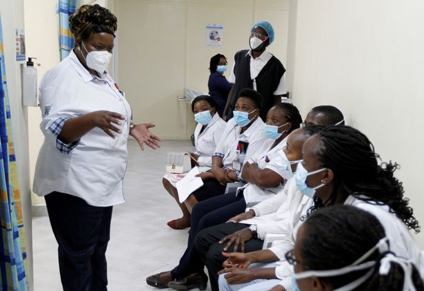 A health worker talks to her colleagues as they prepare to receive the AstraZeneca/Oxford vaccine