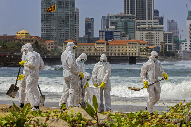 Members of Sri Lankan Navy remove debris washed ashore from the Singapore-registered container ship MV X-Press Pearl, which has been burning for the 12th consecutive day in the sea off Galle Face Beach in Colombo on May 31, 2021. (Photo by Ishara S. KODIKARA / AFP) (Photo by ISHARA S. KODIKARA/AFP via Getty Images)