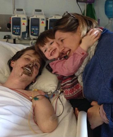 Alex in hospital being visited by wife Lucy and son Sam