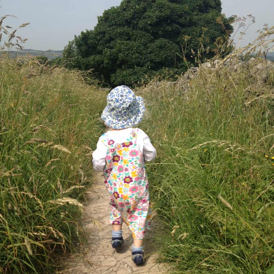 Child walking in grassland on the Monsal Trail, Derbyshire, UK.