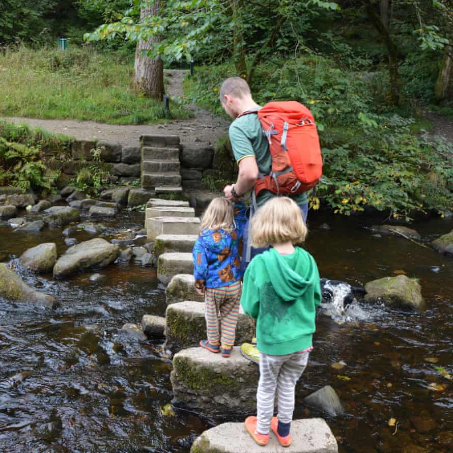 Two children and an adult cross a stream using stepping stones, Hardcastle Crags, West Yorkshire, UK.