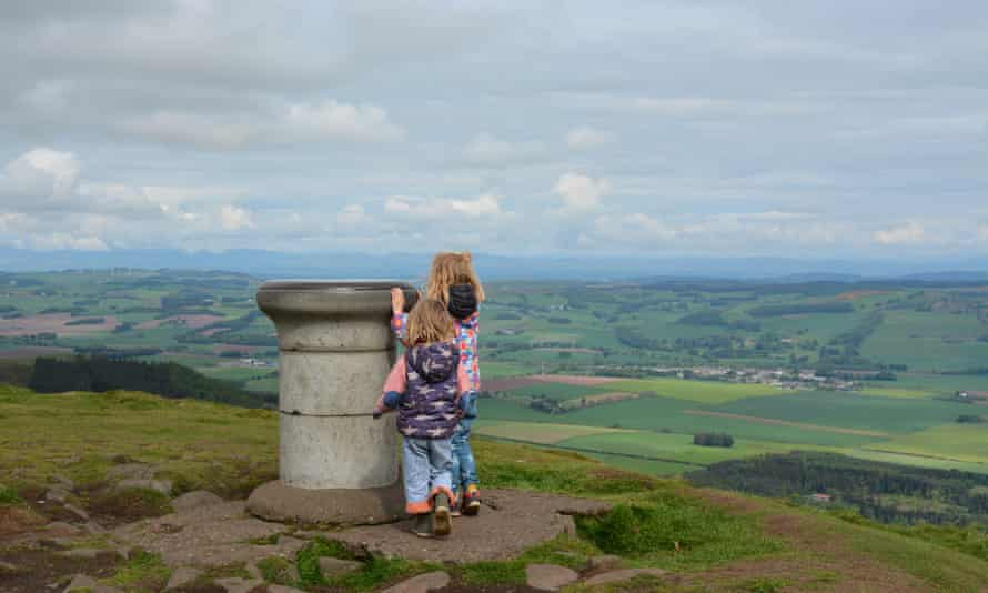 Kids at the to of a hill looking at a monument, East Lomond, Fife.