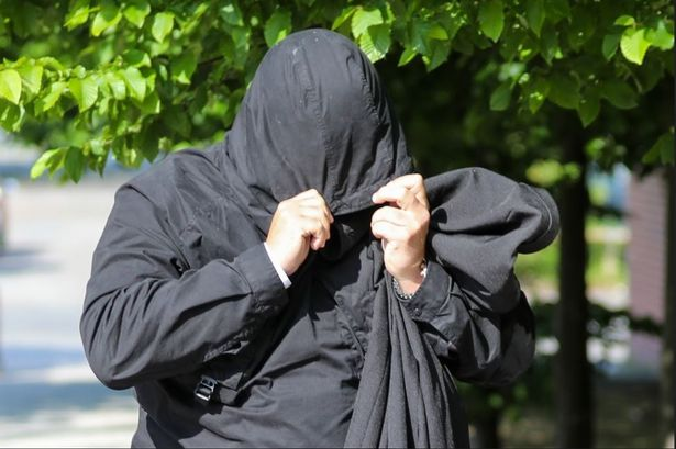 Burke covers up as he leaves court