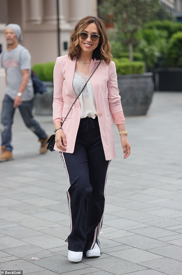 Stunning:Myleene teamed her chic attire with a pair of navy blue trousers that had pink racer stripes to complement her jacket