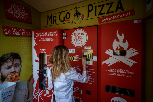 ROME, ITALY - JUNE 07: A girl inserts money into the Mr. Go Pizza vending machine, on June 7, 2021 in Rome, Italy. Mr. Go Pizza is the first automatic pizza vending machine, open 24/7, which is capable of kneading, seasoning and cooking the pizza in three minutes. (Photo by Antonio Masiello/Getty Images)