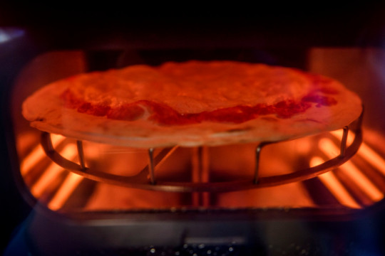 ROME, ITALY - JUNE 07: A general view shows a pizza being cooked at the first Mr. Go Pizza vending machine, on June 7, 2021 in Rome, Italy. Mr. Go Pizza is the first automatic pizza vending machine, open 24/7, which is capable of kneading, seasoning and cooking the pizza in three minutes. (Photo by Antonio Masiello/Getty Images)