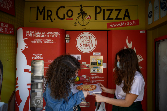 ROME, ITALY - JUNE 07: People get their pizza from Mr. Go Pizza vending machine, on June 7, 2021 in Rome, Italy. Mr. Go Pizza is the first automatic pizza vending machine, open 24/7, which is capable of kneading, seasoning and cooking the pizza in three minutes. (Photo by Antonio Masiello/Getty Images)