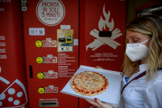 ROME, ITALY - JUNE 07: A girl gets her pizza from Mr. Go Pizza vending machine, on June 7, 2021 in Rome, Italy. Mr. Go Pizza is the first automatic pizza vending machine, open 24/7, which is capable of kneading, seasoning and cooking the pizza in three minutes. (Photo by Antonio Masiello/Getty Images)