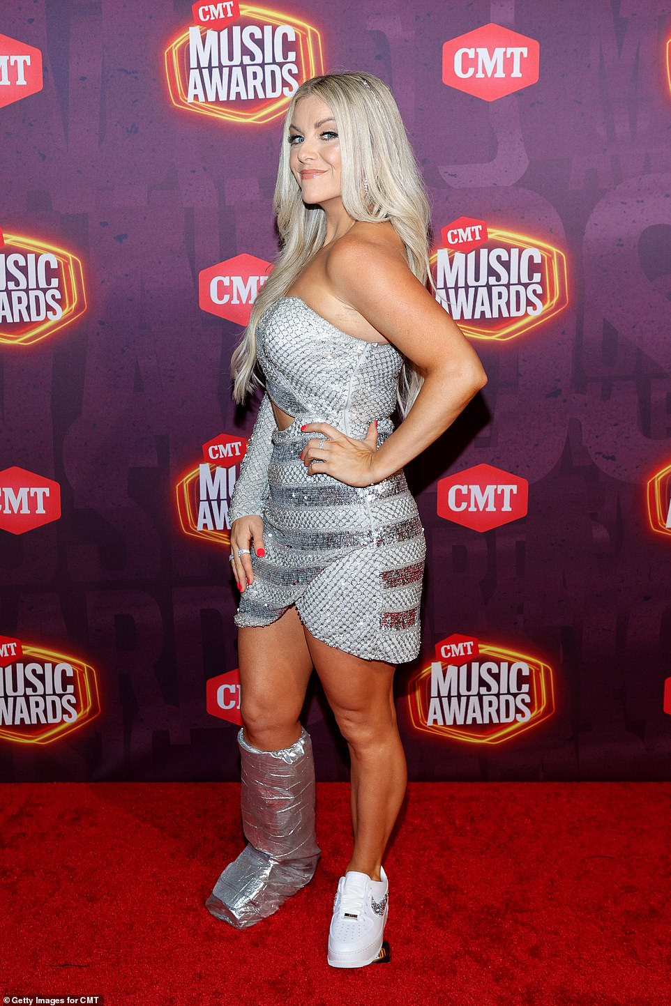 Making it work:Lindsay Ell did not her recent injury get her down by decking out her boot to match her showy silver dress