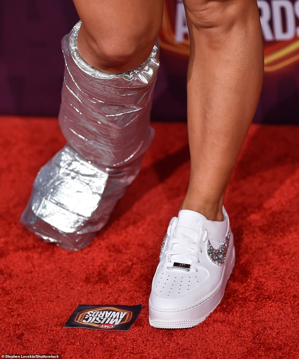 Nailed it:The Canadian singer, 32, wrapped her boot in chrome toned tape, which perfectly coordinated with the sequin detailing on her dress