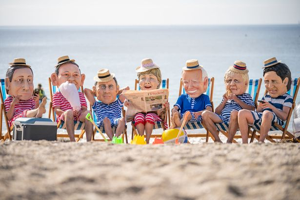 Oxfam campaigners pose as G7 leaders on Swanpool Beach near Falmouth, Cornwall
