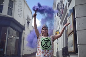 An Extinction Rebellion environmental activist lights a flare during a protest in the streets of Falmouth, Cornwall during the G7 summit on June 12, 2021.