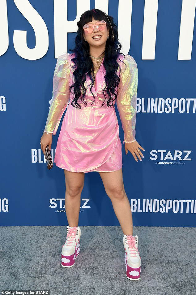 Pretty in pink:Executive producer Jess Wu Calder was unmissable in a lustrous pink mini dress with puffy sleeves, plus platform sneakers and pink-tinted heart-shaped glasses