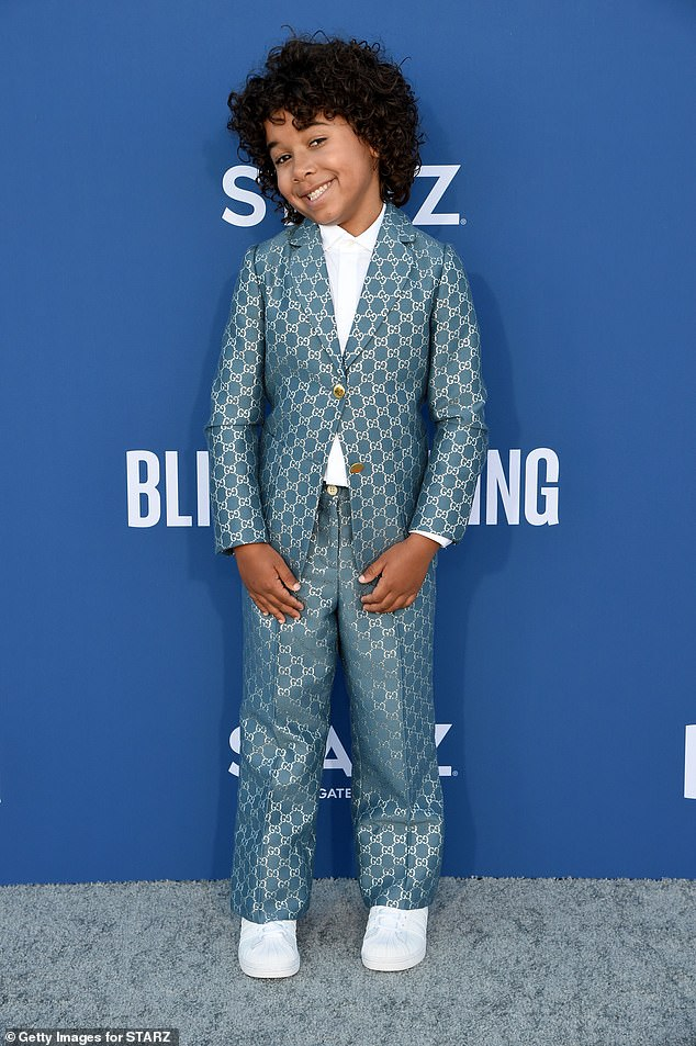 Rising star:Atticus, who plays Jasmine's son Sean, was dressed to the nines in a teal Gucci suit covered in the label's recognizable chain-link pattern, which he paired with low-key white trainers
