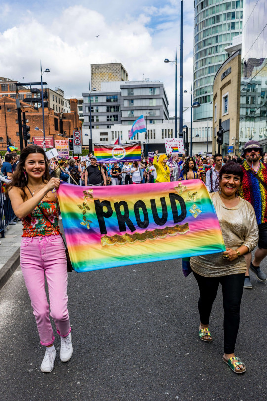 Members of the LGBTQ community are seen holding a banner saying proud during the Birmingham Pride parade