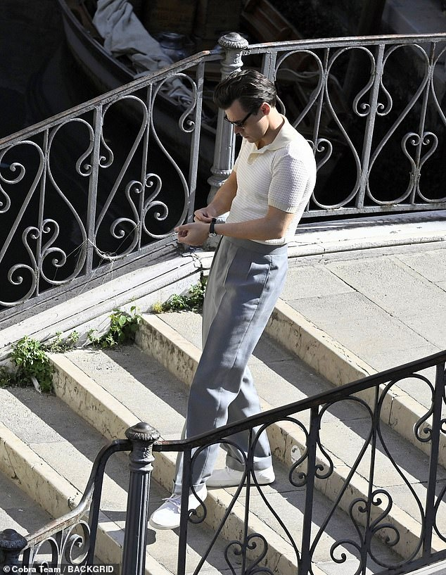 One step at a time: Harry fiddled with his watch as he made his way down the steps of one of Venice's many beaches
