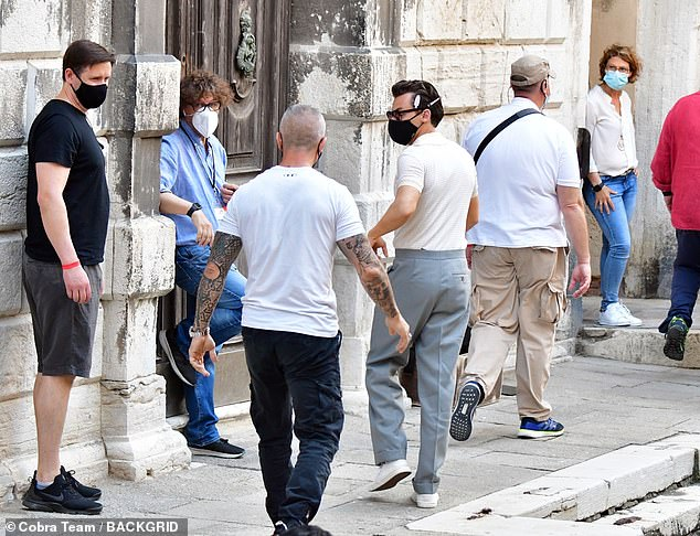 Busy busy: Harry was surrounded by many members of production as filming got underway in Venice
