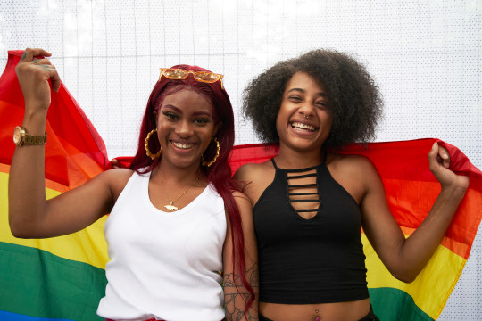 two LGBT women stand with a pride flag