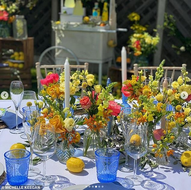 Chic: The outdoor table featured vases full of summery flowers, candles and a stylish dining set-up