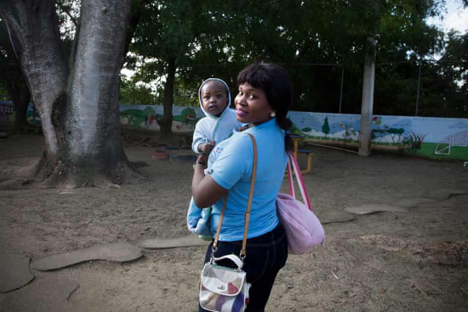 Geralda November, 31, enters the CODEVI textile factory with her 10-month-old daughter, Dorine.