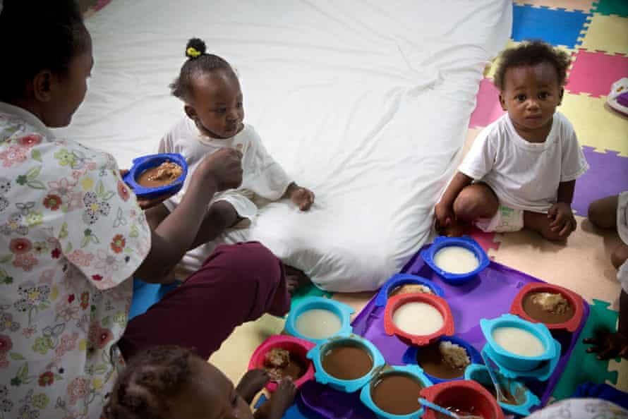 Metelus Anouse feeds 10-month-old Dorine at the Codevi textile factory's daycare centre where Dorine's mother, Geralda, works.