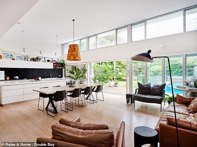Features: It also includes a recently built outdoor swimming pool and spa, plus a basketball net. Pictured: the open-plan living and kitchen area