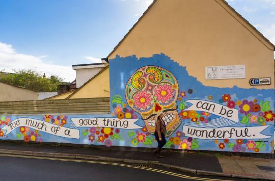 CXX1M6 Mural street art on a wall in Glastonbury, Somerset, UK - skull / day of the dead